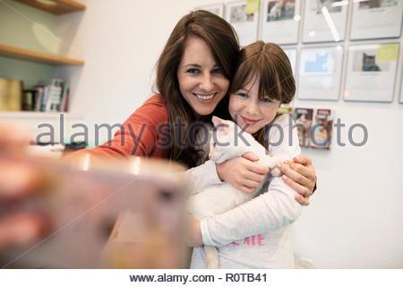Mutter und Tochter halten Kätzchen und unter selfie mit smart phone in Tierheim - Stockfoto