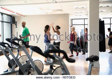 Frauen, high-fiving in Spin Klasse in der Turnhalle - Stockfoto