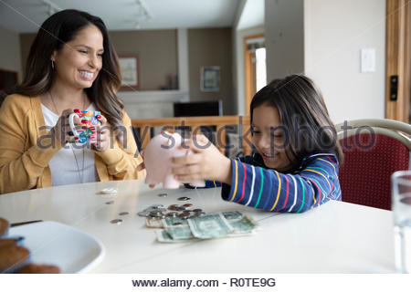 Mutter, Sohn Entleerung piggy Bank - Stockfoto
