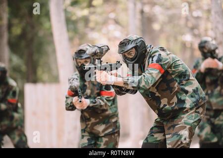 Paintball Team in Uniform und Schutzmasken Ziel von paintballgewehren im Freien - Stockfoto