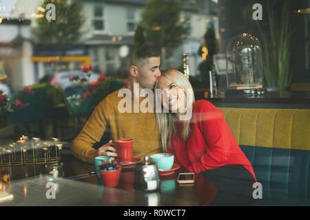 Mann küssen Frau Stirn im Cafe