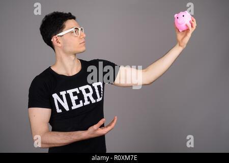 Junge schöne nerd Mann mit Brille gegen grauer Hintergrund - Stockfoto