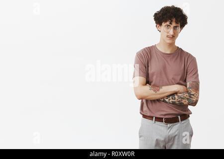 Attraktive tätowiert männliche Gefühl intensiven Verdacht Kerl will Narr ihn um Kreuzung Hände auf der Brust runzelte ernst und besorgt auf Kamera in Gläser und stilvolle urban Outfit - Stockfoto