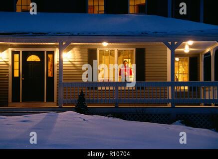 Junge Frau schaut aus gemütlichen Suburban Home Fenster auf frisch gefallenen Schnee, Nordost, USA - Stockfoto