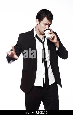 Ein junger Mann in einem schwarzen Anzug mit einer Tasse Kaffee auf einem weißen Hintergrund macht eine Handbewegung. Werbung, Kreativität. Kaffee trinken gehen. - Stockfoto