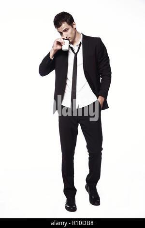 Ein junger Mann in einem schwarzen Anzug mit einer Tasse Kaffee auf einem weißen Hintergrund. Werbung, Kreativität. Kaffee trinken gehen. - Stockfoto