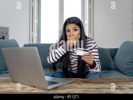 Attraktive junge Latin Frau verzweifelt und wütend mit Kreditkarte und Laptop Standortwahl auf dem Sofa zu Hause in der Kreditkarte Probleme Schulden online Zahlung online - Stockfoto