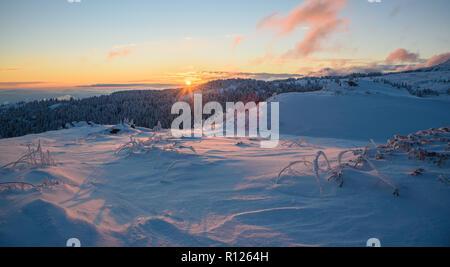 Schönen winter Sonnenaufgang auf einem Berg - gefroren Schönheit mit verschneiten Bäumen, weite Felder in tiefem Schnee und erstaunliche Sunrise - Stockfoto
