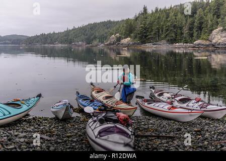 Frau mit Kajaks auf See, Johnstone Strait, Telegraph Cove, Kanada - Stockfoto