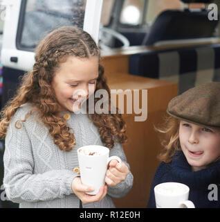 Mädchen trinken heiße Schokolade neben Wohnmobil - Stockfoto