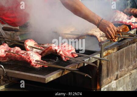Appetitlich köstlich gebratenes Stück Fleisch am Spieß geröstet auf einem großen Grill im Freien. Der Küchenchef bereitet ein Grill. - Stockfoto