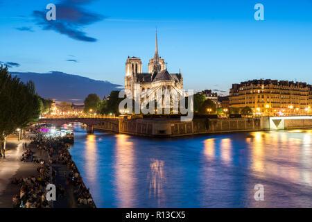 Notre Dame de Paris mit Kreuzfahrt Schiff auf dem Fluss Seine in der Nacht in Paris, Frankreich - Stockfoto