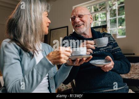 Alte Mann und Frau verbringen Zeit miteinander reden und trinken Kaffee. Senior Paar zusammen zu Hause halten Kaffeetassen an einander suchen Sitzen - Stockfoto