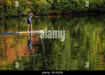 Paddleboarding bei Sonnenuntergang an einem schönen Herbsttag im Stone Mountain Lake in Atlanta, Georgia Stone Mountain Park. (USA) - Stockfoto