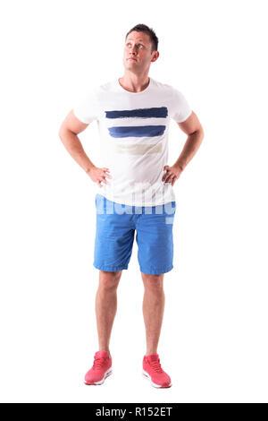 Verwirrt legerer Mann in sportliche Kleidung suchen, um sich mit den Armen auf den Hüften. Voller Körper auf weißem Hintergrund. - Stockfoto