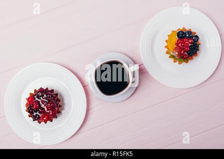 Zusammensetzung der leckere kleine Kuchen mit Espresso auf rosa Holz- Tabelle, Ansicht von oben. Flach Anordnung von schwarzen Kaffee und Berry Törtchen. - Stockfoto