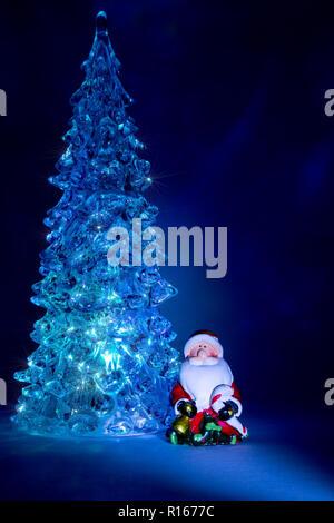 Weihnachtsbaum Spielzeug glänzend mit einem schönen Schatten Northern Lights Hintergrund und Highlights in Form von Sternen mit einem Spielzeug Weihnachtsmann - Stockfoto