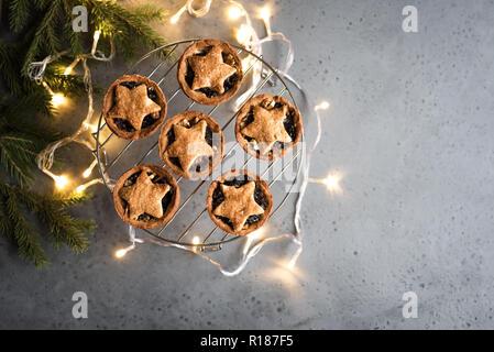 Mince Pies für Weihnachten auf grauem Hintergrund mit Licht und festliches Dekor, kopieren. Traditionelle Weihnachten Dessert - Kuchen mit Früchten und Nüssen vor den Mund. - Stockfoto