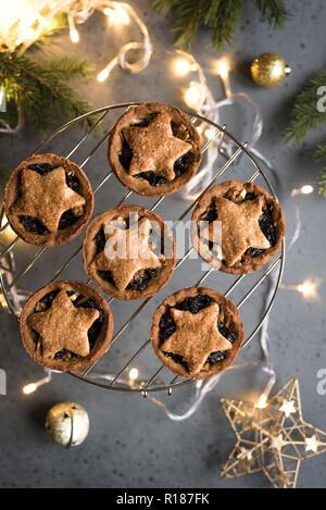 Mince Pies für Weihnachten auf grauem Hintergrund mit Licht und festliche Dekoration. Traditionelle Weihnachten Dessert - Kuchen mit Früchten und Nüssen vor den Mund. - Stockfoto