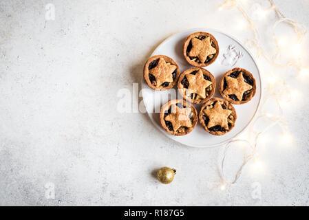 Mince Pies für Weihnachten auf weißem Hintergrund mit Licht, kopieren. Traditionelle Weihnachten Dessert - Kuchen mit Früchten und Nüssen vor den Mund. - Stockfoto