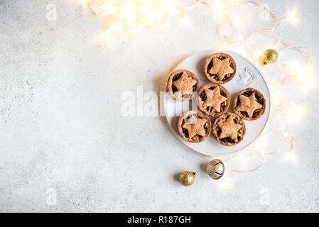 Mince Pies für Weihnachten auf weißem Hintergrund mit Licht, kopieren. Traditionelle Weihnachten Dessert - obstkuchen Hacken. - Stockfoto