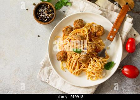 Italienisches Pastagericht. Spaghetti mit Hackbällchen mit Tomatensauce auf Stein oder Beton. Ansicht von oben flach Hintergrund. Kopieren Sie Platz. - Stockfoto