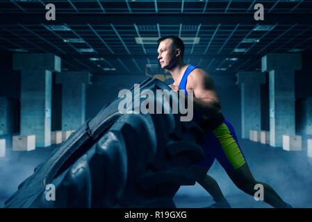Starke männliche Athlet tun Krafttraining mit lkw-reifen in der Turnhalle, crossfit Workout. Cross fit Training im Sport Club - Stockfoto