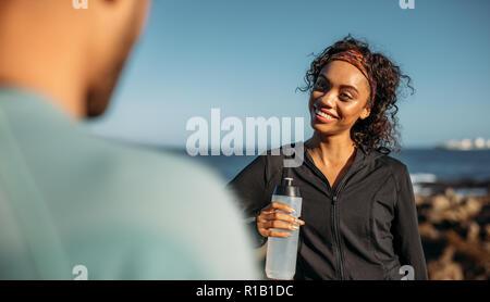 Lächelnde Frau entspannend nach einem Workout Trinkwasser. Frau geht zu ihrem Freund nach dem Training stehen im Freien. - Stockfoto