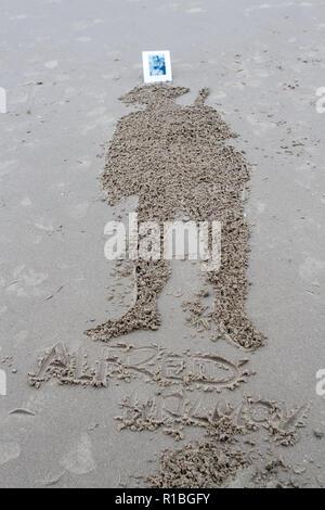 Blackpool, Lancashire, UK. 11 Nov, 2018. Erinnerung Sonntag. Menschen versammeln sich für eine Morgendämmerung Gedenktag zu Ehren der Gefallenen der Weltkriege. Sand Skulpturen werden in den Sand geschnitzt als Schatten der Vergangenheit, daran zu erinnern, daß alle gaben einige & einige Alle gab heute für unsere Freiheiten. Sie sind abgewaschen werden, da die Flut kommt, als die Menge Wellen eine kollektive Auf Wiedersehen. Credit: cernan Elias/Alamy leben Nachrichten - Stockfoto