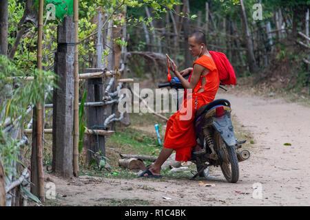 Don Det, Laos - April 23, 2018: Junge buddhistische Mönch sitzt auf einem Roller und über sein Smartphone in einem abgelegenen Dorf im südlichen Laos - Stockfoto