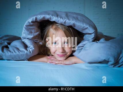 Lächelnd und fröhlich süsse kleine Mädchen suchen glücklich im Bett in der nacht oder morgen Gefühl Freude und Ruhe in der Schlafkomfort, glückliche Familie und Kinder