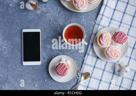 Kuchen mit Sahne in einem Teller, Tasse Kaffee, auf einem grauem Marmor tisch Frühstück Desktop smartphone - Stockfoto