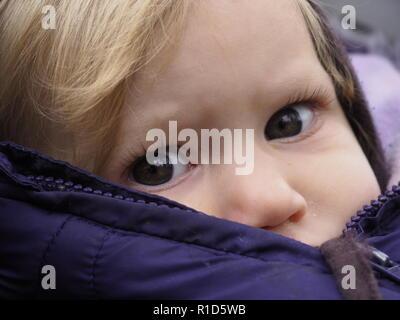 Blond kaukasische Baby Mädchen mit grauen Augen im Winter Jacke an Kamera suchen - Stockfoto
