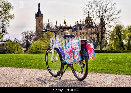 Kinder Fahrrad mit satteltaschen im Park, mit Schweriner Schloss im Hintergrund. - Stockfoto