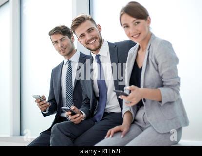 Lächelnde Angestellte mit ihren Smartphones. - Stockfoto