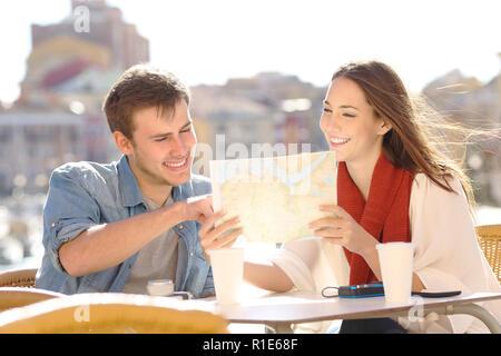 Paar Touristen finden Lage in einer Karte in einem Café, einer Küstenstadt im Urlaub - Stockfoto