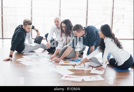Junge kreative Menschen in modernen Büro. Die Gruppe junger Geschäftsleute gemeinsam mit Laptop. Freiberufler sitzen auf dem Boden. Zusammenarbeit corporate Achievement. Teamwork Konzept - Stockfoto