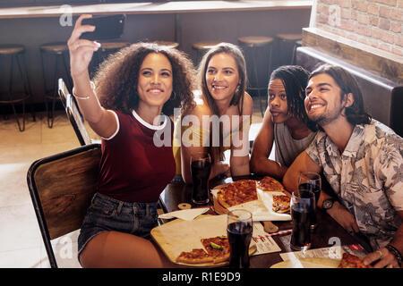 Junge Frau von selfie mit Freunden im Restaurant sitzen. Gruppe von multi-ethnischen Freunden im Cafe Erfassen einer selfie in Smart Phone. - Stockfoto