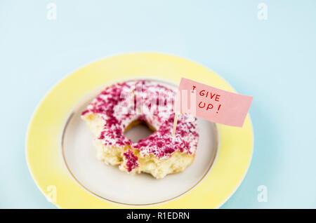 Die Hälfte gegessen Donut mit weißen und rosa Zuckerguß auf gelb Platte mit Hingabe Flagge Text: ich gebe auf, auf blauem Hintergrund. Studio konzeptionelle Schuß des Wir - Stockfoto