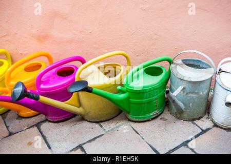 Alten und gebrauchten Kunststoff und Metall Gießkannen und Töpfe in verschiedenen Farben für die Bewässerung von Pflanzen und Blumen im Haus und Garten stehen auf einem Steine in der Nähe von - Stockfoto