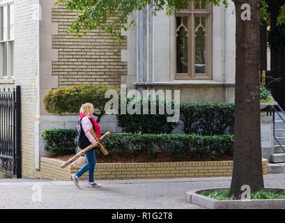 CHARLOTTE, NC, USA -11/08/18: Frau, die ein hölzernes Kreuz auf Tryon Street. - Stockfoto