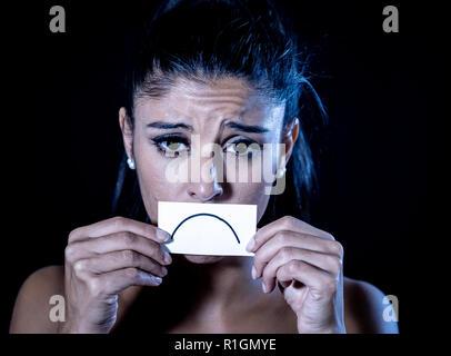 Close up Portrait von traurigen attraktive junge Latin Frau unter Depressionen leiden in dramatische Beleuchtung auf schwarzem Hintergrund isoliert. - Stockfoto