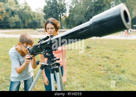 Kinder und jugendliche mit einem teleskop schauen sie in den himmel