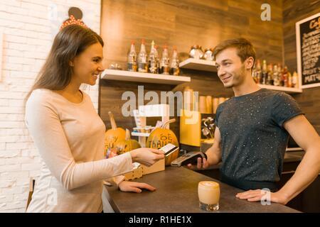 Mädchen Coffee Shop Kunde zahlt Kaffee per Kreditkarte, barista Holding a credit card reader Maschine. - Stockfoto