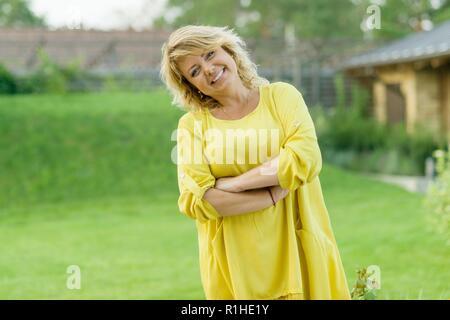 Outdoor Portrait von positiven reife Frau mittleren Alters, weiblich mit verschränkten Armen, schönes Lächeln, Hintergrund Garten. - Stockfoto