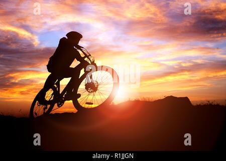 Mountain Biker Silhouette gegen den Sonnenuntergang Konzept für Leistung, Widrigkeiten zu erobern und die Ausübung der - Stockfoto