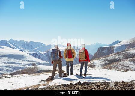 Drei Touristen steht auf dem Gipfel des Berges vorbei und schaut anzeigen - Stockfoto