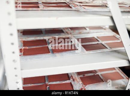 Tafeln Schokolade Kühlung in Kunststoffformen auf einem Regal - Stockfoto