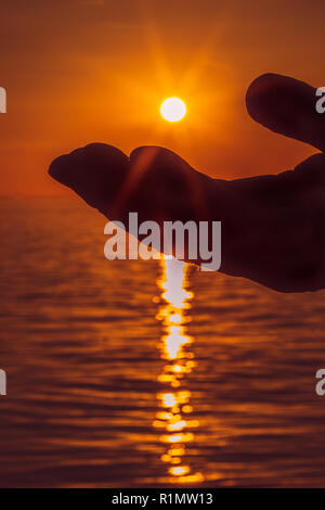 Silhouette einer Palme einer Hand fast berühren die untergehende Sonne über einem Ozean. Die Strahlen der Sonne kann man scheint über die Hand und plätschern in Th. - Stockfoto