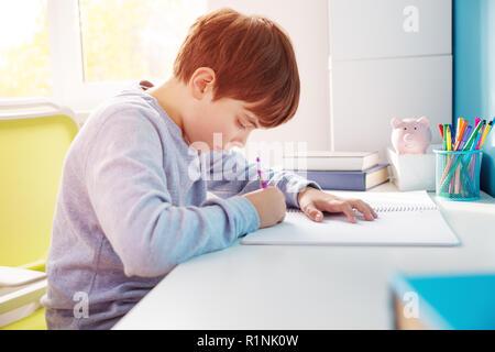 Neun Jahre altes Kind zu Hause schreiben Stockfoto